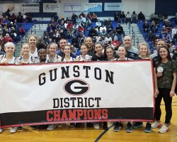 Girls and coaches standing behind banner saying Gunston District Champions