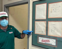 CEO, wearing a mask, pointing to Krispy Kreme display on wall of the fire station