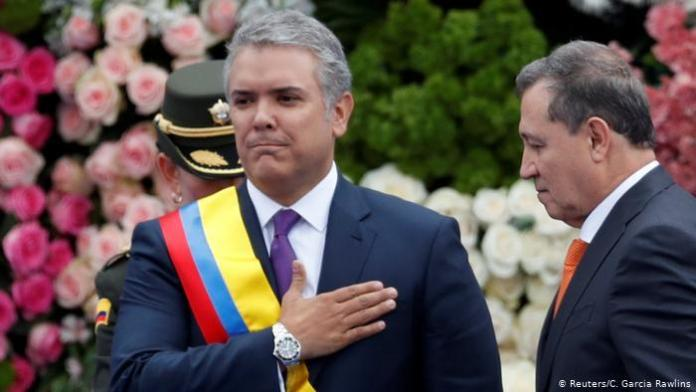 Colombia's new President Ivan Duque salutes to the audience after receiving the presidential sash from President of the Senate Ernesto Macias, during his inauguration ceremony at the Bolivar Square, in Bogota