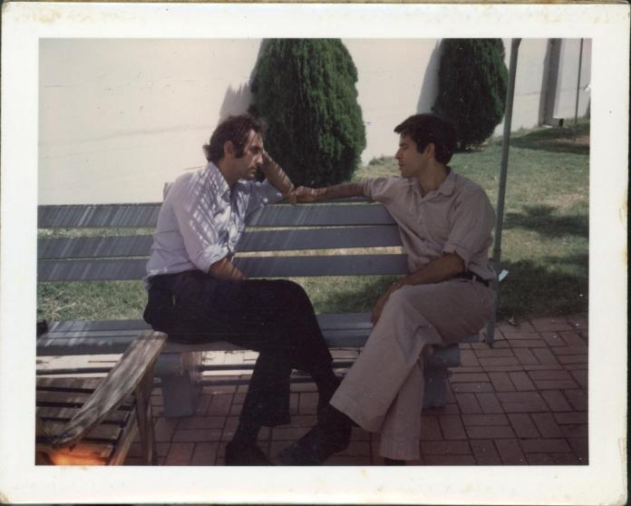 A couple of men sitting on a bench Description automatically generated with low confidence