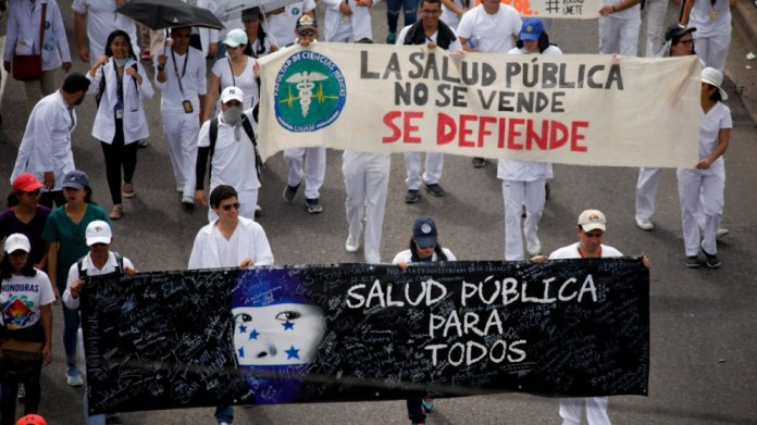 """Demonstrators march during a protest against the government of Honduras' President Juan Orlando Hernandez in Tegucigalpa, Honduras, Thursday, May 30, 2019. Thousands of doctors and teachers have been marching through the streets of Honduras' capital for the last three weeks, against presidential decrees they say would lead to massive public sector layoffs. The banners carried by the demonstrators read in Spanish """" Public health for all"""" and """"Public health is not for sale. We will defend it."""""""