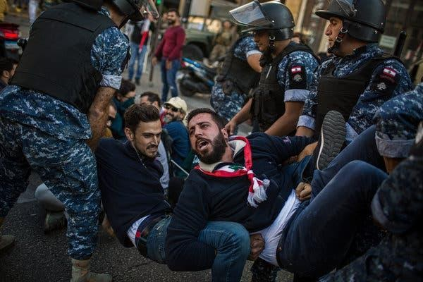Riot police officers removing antigovernment protesters from an intersection in Beirut.