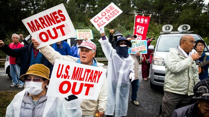 Residents holding placards reading US Military out protect the relocation of the new U.S Marine Airbase construction on...