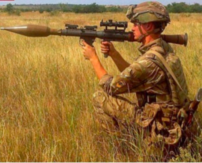 A soldier holding an object  Description automatically generated with low confidence