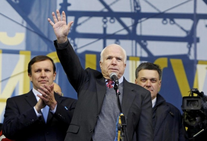 Image:  Sen. John McCain waves to pro-European protesters during a rally at Independence Square in Kiev in December