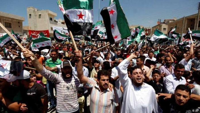 Syrians attend an anti-Bashar Assad protest after Friday prayers on the outskirts of Idlib, Syria, Friday, June 8, 2012.