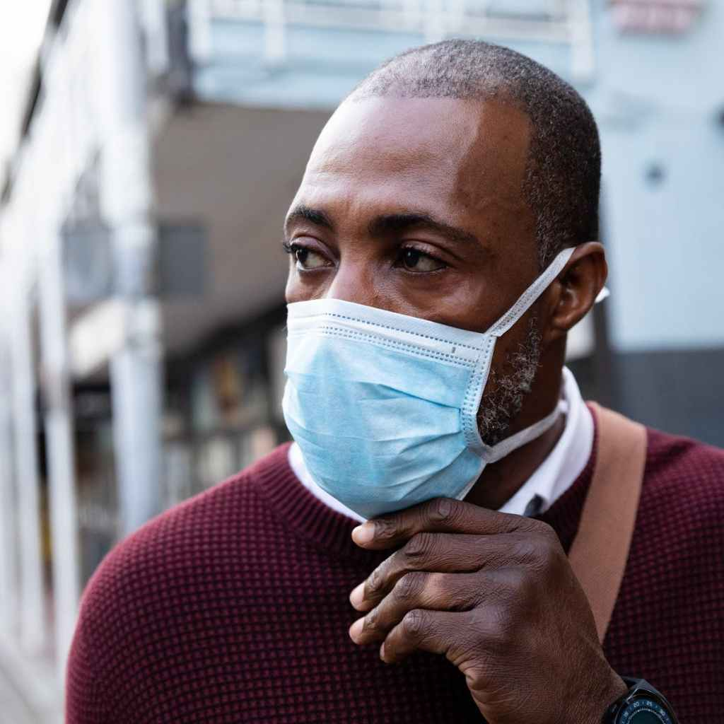 An African American man wearing a surgical mask