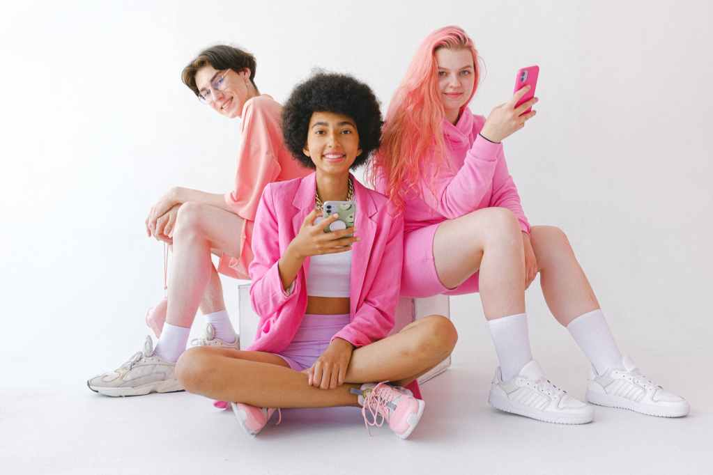 cheerful multiracial teenagers in trendy outfit with smartphones