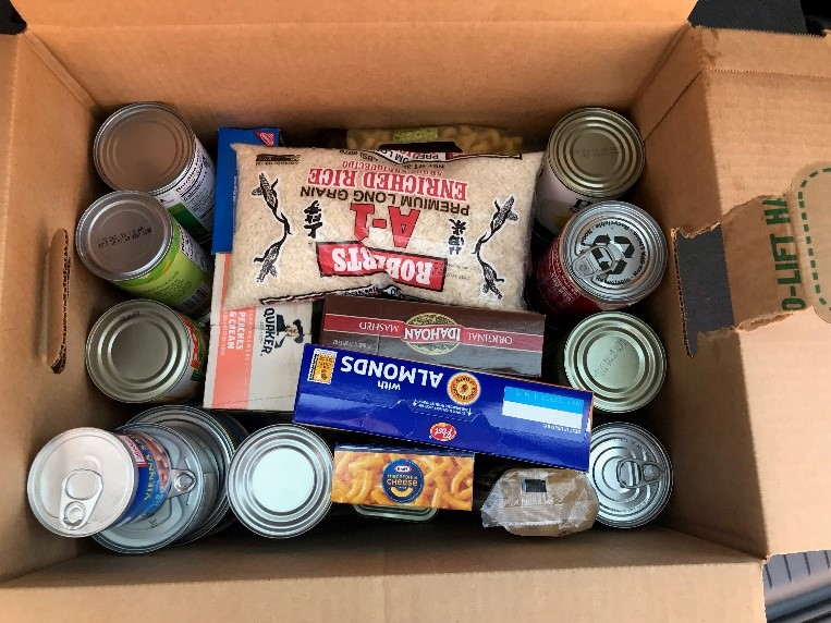Cardboard box with many cans, boxes of macaroni and cheese, almonds and mashed potatoes, a bag of rice and oatmeal.