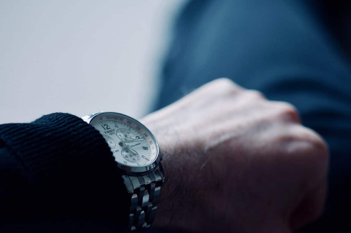 Photo of hand and Tissot wrist watch with focus on the time in cold blue colours ageing us