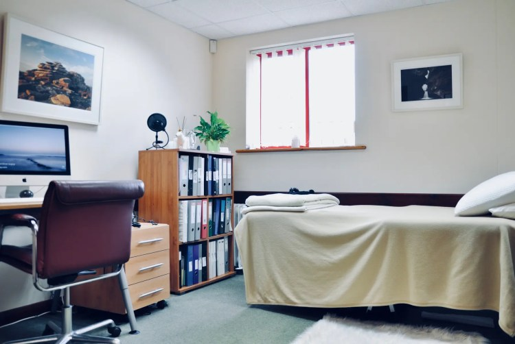 Photo of Neil Cox Hypnotherapy clinic room Bude Cornwall with therapy couch and bookcase with desk for appointments