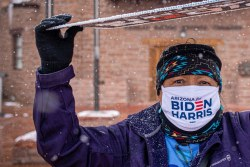 Biden/Harris supporter Cindy Honani stands outside the Navajo Nation Council Chamber while holding a sign above her head to protect herself from the snow in Window Rock in late October. Sharon Chischilly/Navajo Times via The High Country News