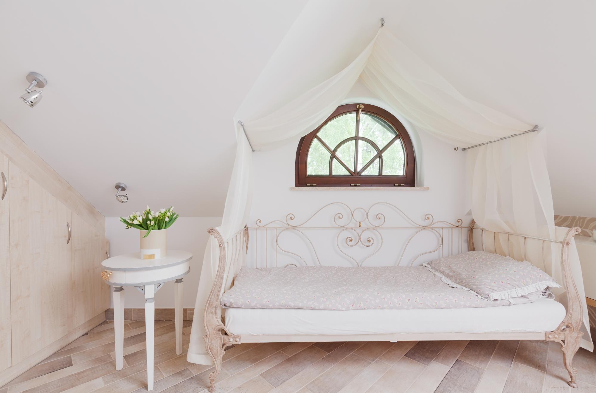 Transparent baldakin ovanför sängen, fäst i taket