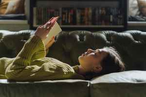 woman in yellow long sleeve shirt lying on couch reading