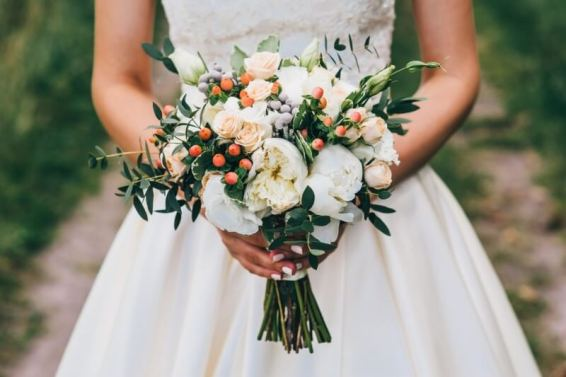 bride holding a bouquet of flowers and berries in a rustic style, wedding bouquet
