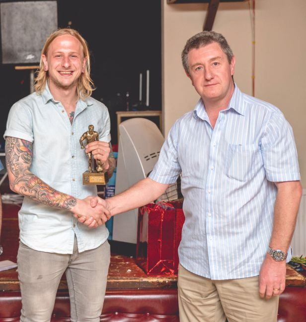 Thomas Davies receives the Players' Player of the Year award from Neil West of Crystal Vision, Ton Pentre.