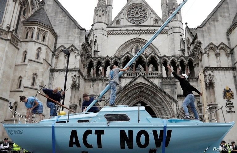 FILE - Extinction Rebellion climate activists raise a mast on their boat during a protest outside the Royal Courts of Justice in London, Britain, July 15, 2019.