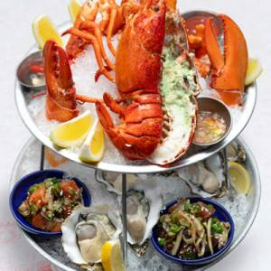 Chilled seafood tower with raw oysters, shrimp cocktail, ahi poke, smoked salmon poke, lomi salmon, whole lobster and king crab legs.