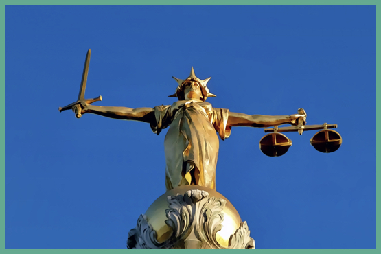 "Golden ""Lady Justice"" sculpture with a blue sky in the background."