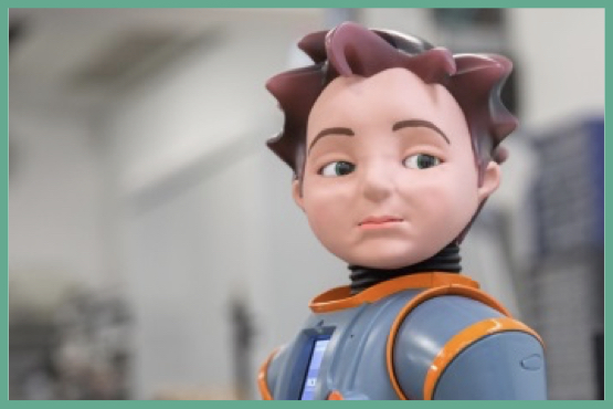 Image of Zeno, a 'human-like' robot with brown hairs and  eyebrows, and a grey/orange outfit.
