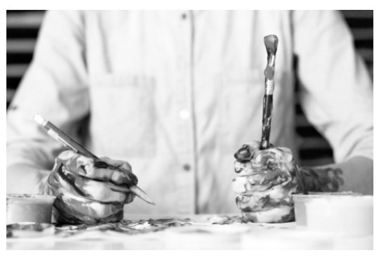 Paint smeared hands holding brushes; their owner is wearing a clean white shirt.