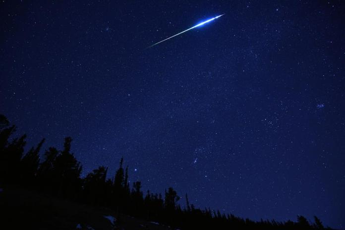 A green-glowing meteor from the annual Geminids meteor shower.