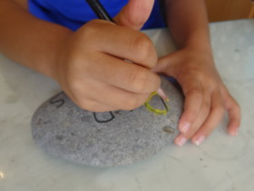 Kids drawing on rock
