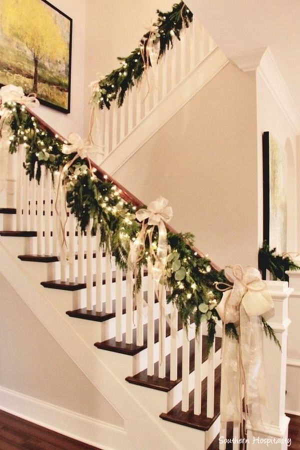 Beautiful christmas decor with natural garland, white lights, gold bows draped on handrail of staircase.