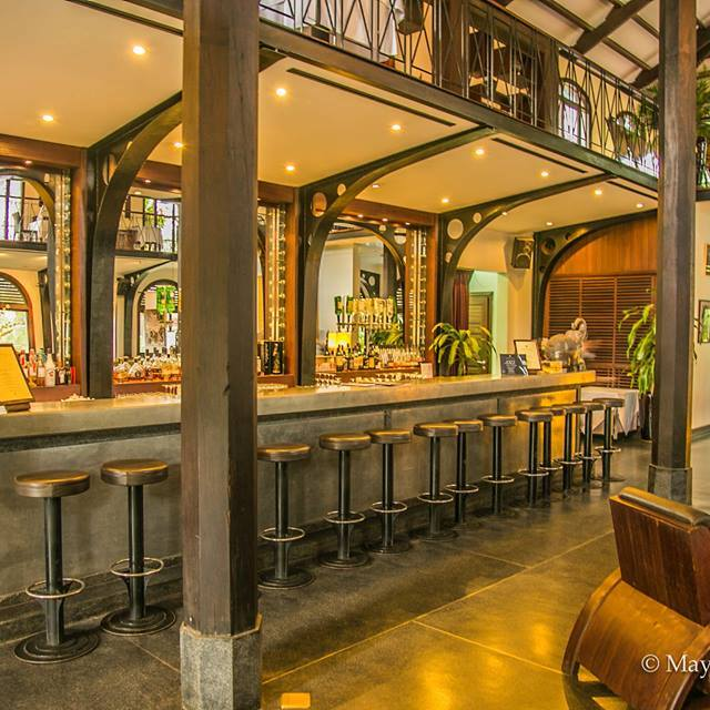 Heritage Suites Hotel luxury travel public relations case study lobby bar with wooden furniture, a row of bar stools, alcohol bottles, beams and mirrors.