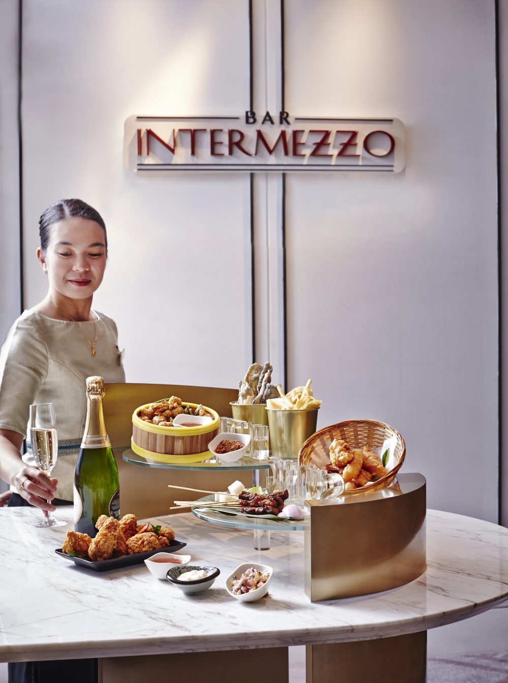 Digital Agency Case Study - Orchard Hotel Singapore - Bar Intermezzo bar bites and champagne; waitress dishing out food like fried chicken, satay and glasses