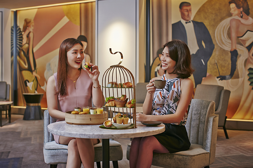 Digital Agency Case Study - Orchard Hotel Singapore - Afternoon Tea at Bar Intermezzo with two girls enjoying snacks from a halved bird cafe with 3 tiers; background is styled after Great Gatsby era