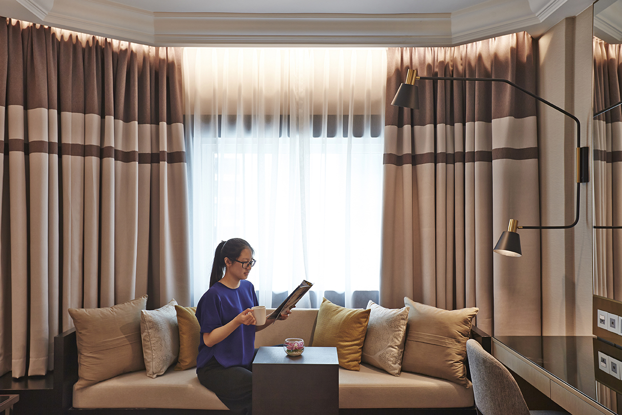Digital Agency Case Study - Orchard Hotel Singapore - girl reading book and seating on sofa in Grand Deluxe Room with beige colour scheme