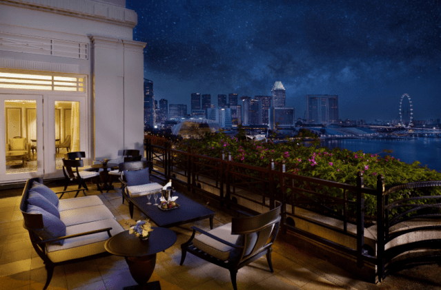 The Fullerton Hotel Singapore's Fullerton Suite has a balcony with sofas chairs and view of Marina Bay and Singapore Flyer. Good for staycation
