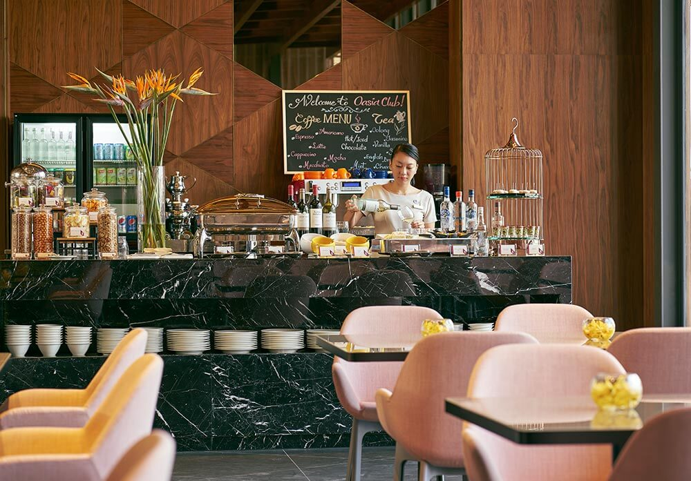 Staycation in Singapore during Phase 2 at the Oasia Hotel Downtown. Upgrade to Club Floor to enjoy this beautiful lounge. A waitress presides over a bar with food and wine and pink chairs.