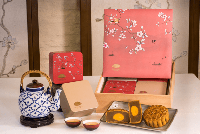 Baked mooncakes in floral box with tea pot as decor