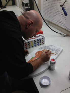 Putting some finishing touches of glitter on his piece.