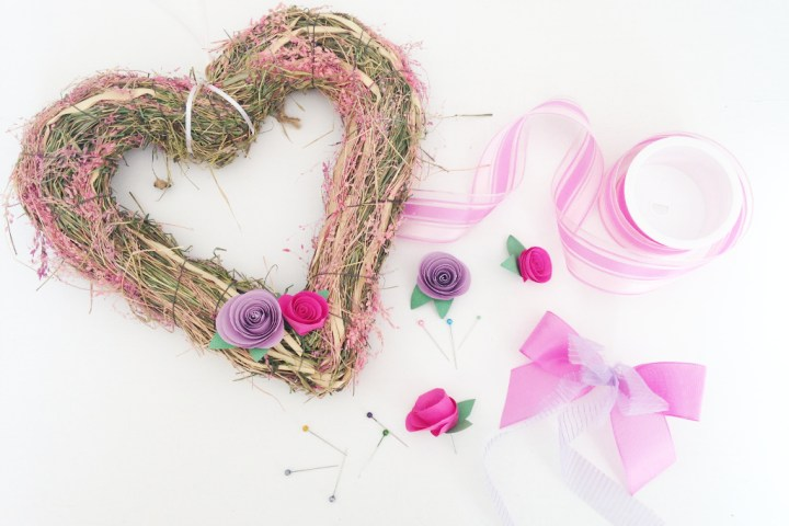 this image shows the supplies needed to make a DIY heart-shaped pink and violet spring wreath with paper roses and a ribbon bow