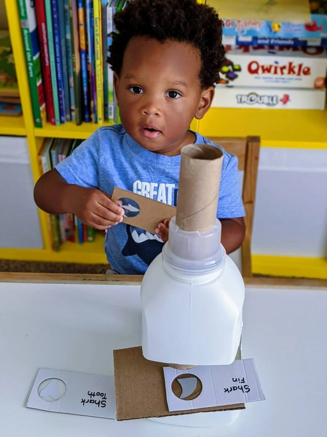 toddler playing with homemade science toy for dramatic play