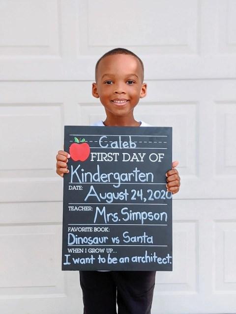 Black Kindergarten student holding a chalkboard sign