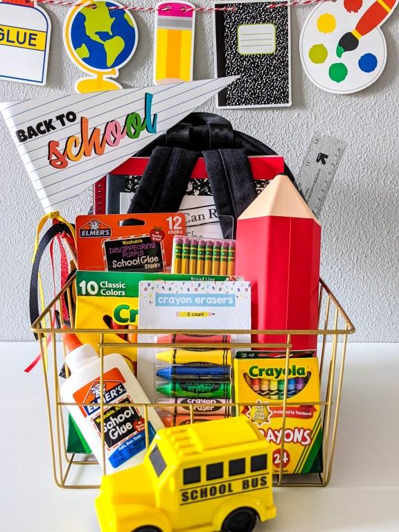 back to school basket for kids including markers, crayons, glue, ruler, pencils