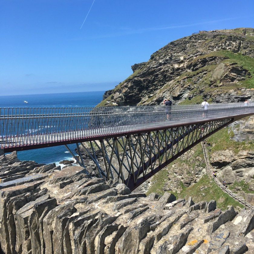 View across to the Tintagel Bridge, with blue skies, sea and horizon in the background