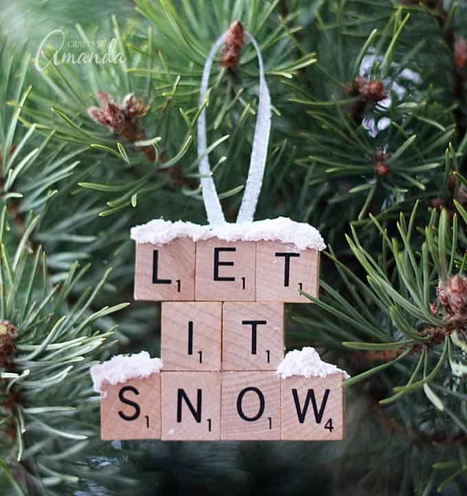 """Make a """"Let It Snow"""" scrabble tile ornament from scrabble tiles and snow texture paint! So easy to make, you will need a paper plate and some felt too, great to give as gifts! A fun Christmas ornament project for kids and adults."""