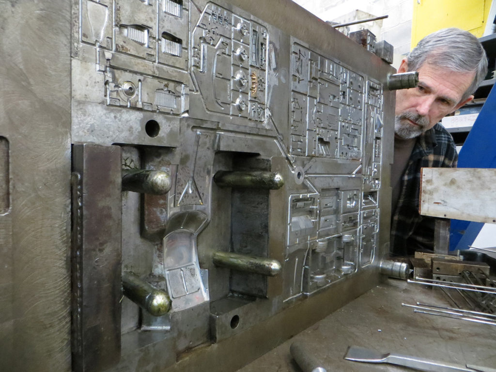 Gerry Humbert examines a mold for a Revell car. The areas for the car's seats, grille and roof are visible in the foreground. The steel support rods keep the steel mold for warping as plastic explodes into the channels at 2,000 lbs. per square inch—roughly the pressure a submarine would experience 4,000' under water, or the weight of 400 compact cars