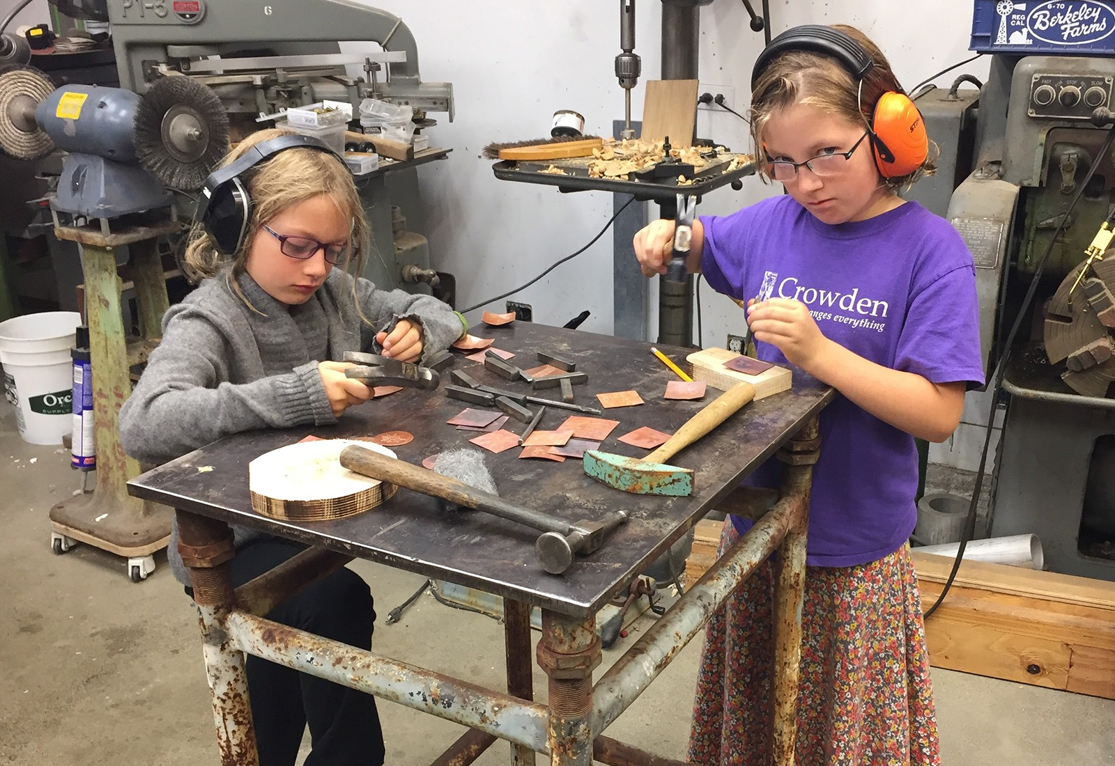 Lilah Lloyd and her twin sister Phoebe use texturing tools to make designs on copper, in their father's garage workshop.