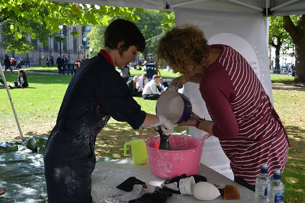 The artist helps a woman pour liquid plaster out of a bowl and into some fabric.