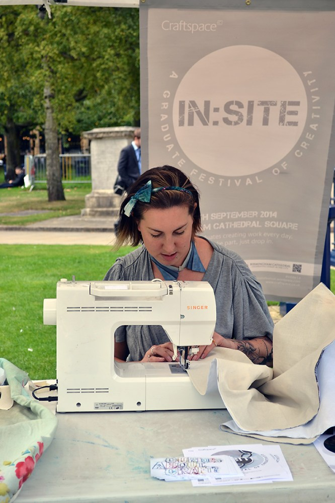 A girl sits at a sewing machine outside in a park.