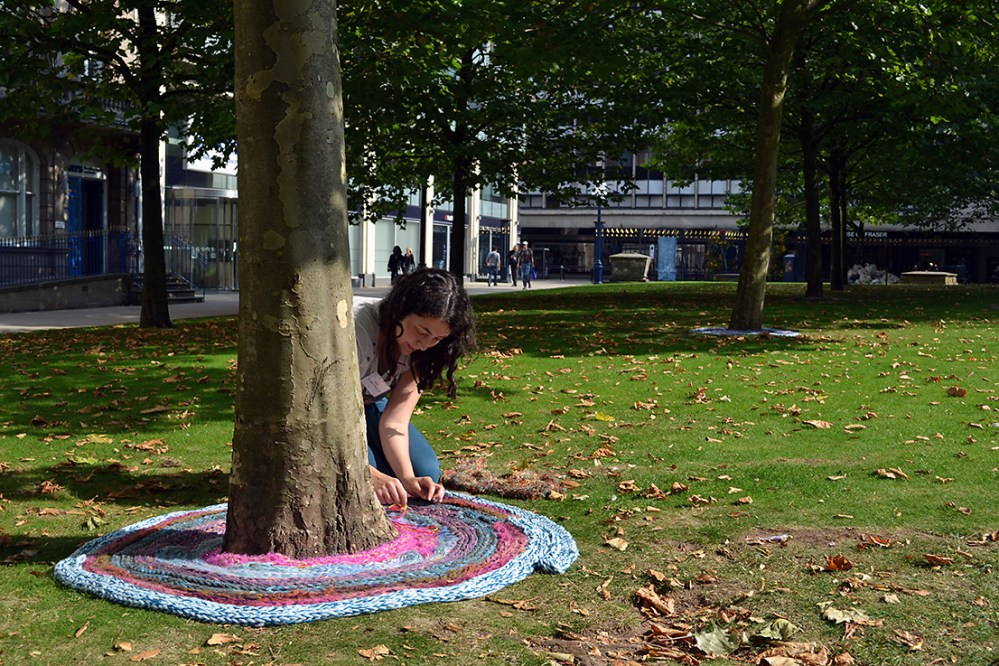 The artist lies the plaited yarn around the tree.