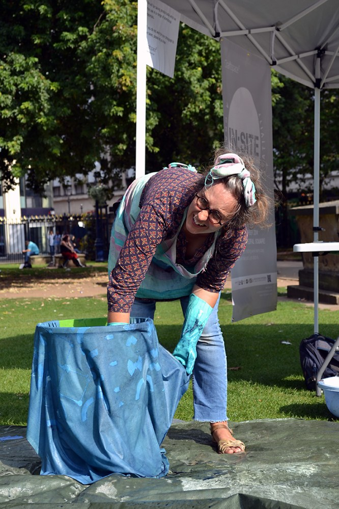 The artist reaches into a large bucket wearing blue gloves.