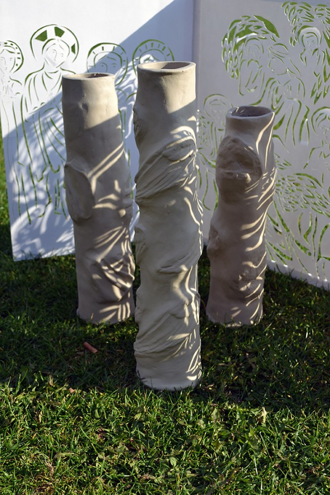 Three clay cylinders carved and manipulated into different shapes sit on the grass with a back drop of cut out paper showing figures from the bible.