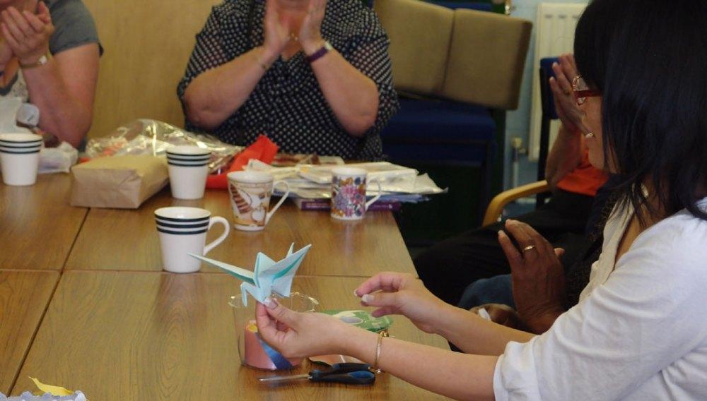 A member of Shelanu teaches participants how to make an origami bird.